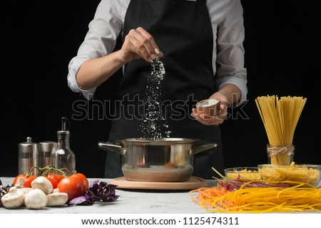 The chef prepares spaghetti and pasta, salt water, against a dark background, the concept of cooking Royalty-Free Stock Photo #1125474311