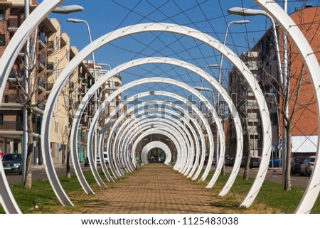 Pedestrian walk through the center of an avenue, protected by a mesh of cables intertwined between white semicircular metal arches that simulate a tunnel  #1125483038