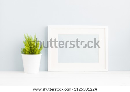 White frame mock up and a plant on a book shelf. #1125501224