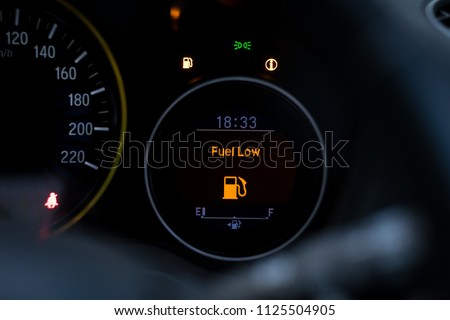 Close up empty Petrol, gasoline gauge dash board in car with digital warning sign of run out of fuel turn on on black background. Low level of fuel show on speedometer dashboard.