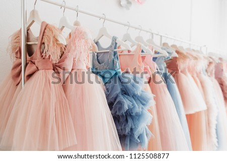 Beautiful dressy lush pink and blue dresses for girls on hangers at the background of white wall. Kids dresses with feathers for prom and holiday. #1125508877