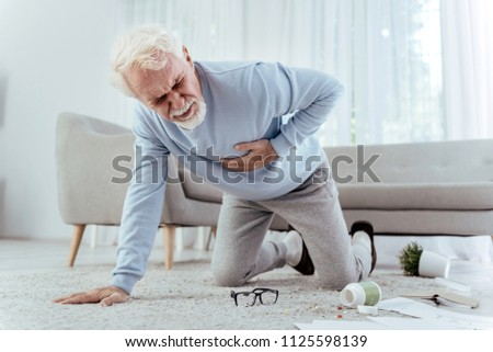 Blood blockage. Ill senior man touching chest and falling on floor #1125598139