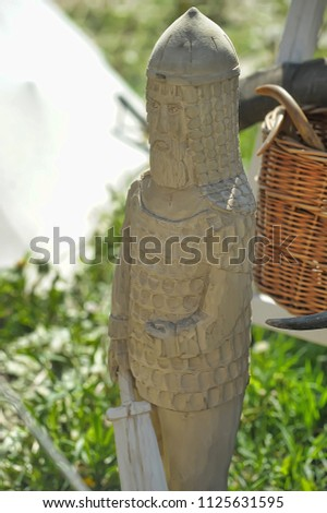 a figure carved from a tree - a hero with a sword, an idol #1125631595