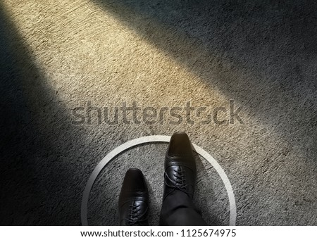 Comfort Zone Concept. Businessman with Formal Shoes Steps over Circle Line to Outside the White Bound. Top View, Dark Tone, Light Shading on Cement Floor #1125674975