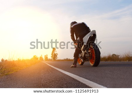 Motorbike riding on road with sunset  #1125691913