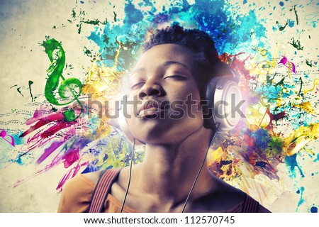 Black girl listening to the music with a pair of headphones Royalty-Free Stock Photo #112570745