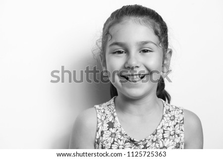 Portrait of a happy smiling child girl. Laughing child. Expressive facial expressions. Black and white image. Space for text. #1125725363
