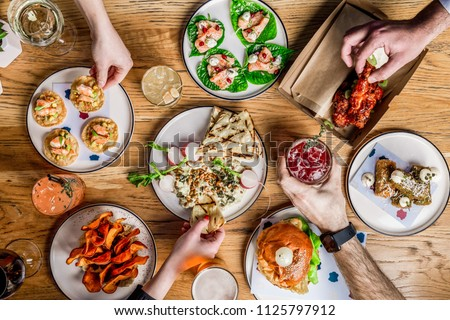 Flat lay bar meals with cocktails and hands #1125797912