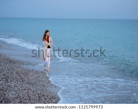 a woman is walking by the sea #1125799973