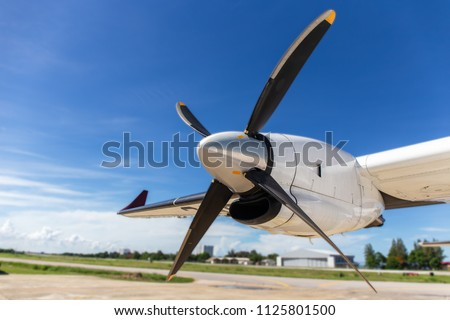 aircraft propeller blade and turboprop engines with airfield, blue sky background and copy space Royalty-Free Stock Photo #1125801500