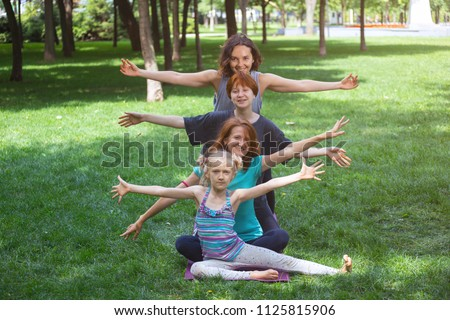Happy fun girls doing yoga in the park on the grass. Healthy and Yoga Concept