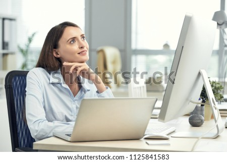 Young charming woman sitting at table in office and looking up in dreams and inspiration #1125841583