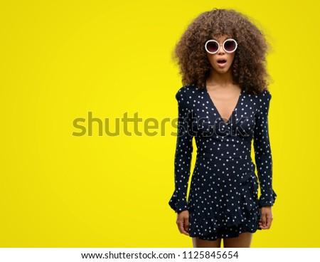 African american woman with sunglasses and summer dress scared in shock with a surprise face, afraid and excited with fear expression #1125845654