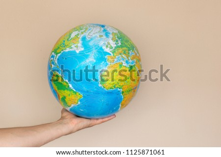 Big color globe on a man's hand on a beige background #1125871061