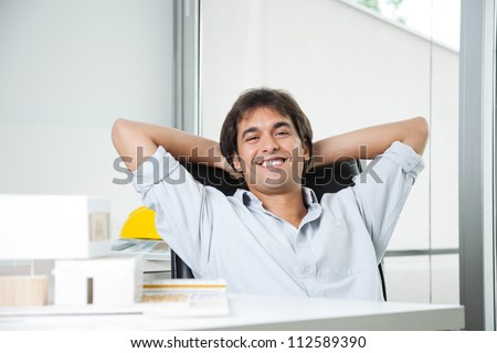 Portrait of a relaxed male architect sitting in chair with hands behind head #112589390