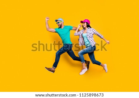 Portrait of athletic sportive students running fast wearing jeans casual clothes isolated on bright yellow background. Inspiration motivation concept #1125898673