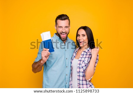 Portrait of successful lucky couple getting visa abroad holding raised fist showing passport with flying tickets shouting with wide open mouth isolated on vivid yellow background #1125898733