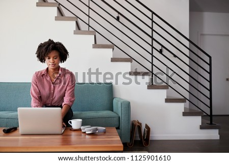Woman Sitting On Sofa At Home Using Laptop Computer #1125901610