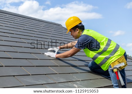Roof repair, worker with white gloves replacing gray tiles or shingles on house with blue sky as background and copy space, Roofing - construction worker standing on a roof covering it with tiles. #1125915053
