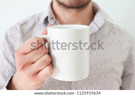 Man with white shirt is holding white coffee mug in his right hand #1125919634