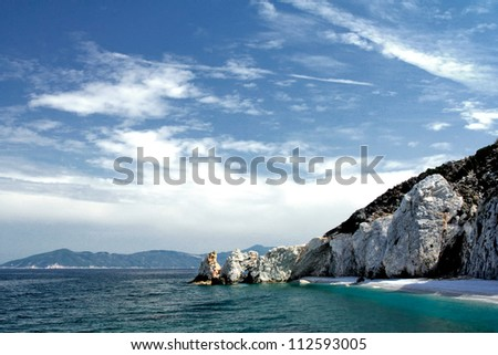 rocky beach in greece with blue water and sky #112593005