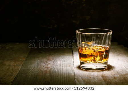 Scotch on wooden background with copyspace. An old and vintage countertop with highlight and a glass of hard liquor #112594832