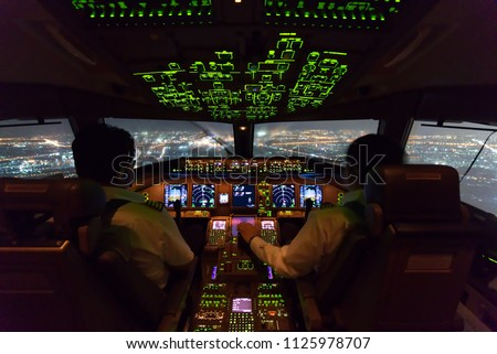 Two pilots are flying the airplane in approach phase to the runway in night time while raining. Cityscape and airport are seen outside cockpit. Pilots and airplane instruments are inside cockpit. #1125978707