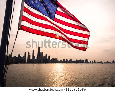 A beautiful picture of an American Flag rippling in the wind over the Chicago skyline at sunset with building silhouettes and sun reflecting on the water of Lake Michigan.
