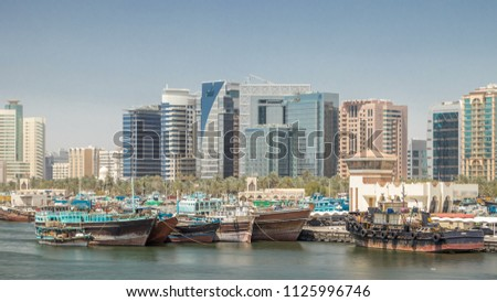 Trading wooden boats in the port timelapse. Merchant ships on the Creek Canal. Skyscrapers on background. View form bridge #1125996746