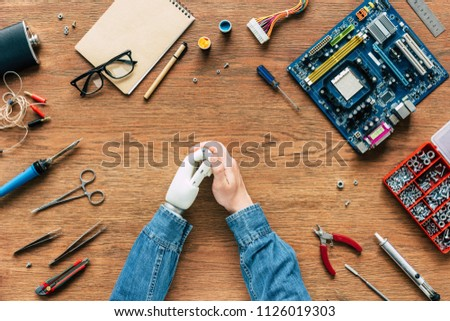cropped image of electronic engineer with robotic hand sitting at table with instruments and motherboard #1126019303