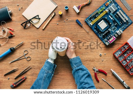 cropped image of electronic engineer with prosthetic arm holding paper cup on table with tools #1126019309