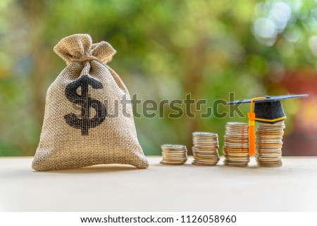Education expense or student loan for post secondary education concept : Dollar bag, graduation cap on row of coins on a table, depicts loan or money designed to help students pay for associated fees #1126058960