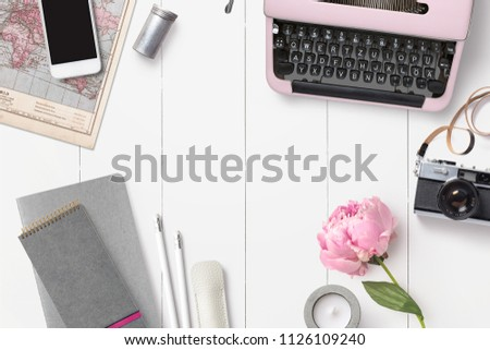 styled feminine desk background with various writing supplies, vintage camera and pink peony - top view, copyspace for your text