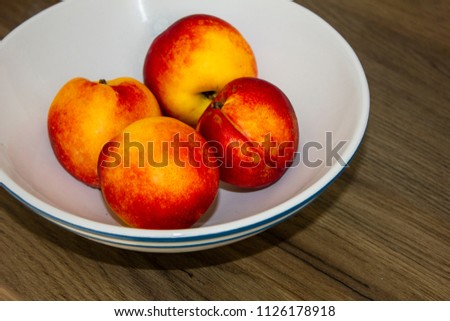 several bright juicy nectarines in the white bowl on wooden table #1126178918
