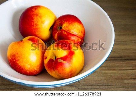 several bright juicy nectarines in the white bowl on wooden table #1126178921