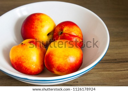 several bright juicy nectarines in the white bowl on wooden table #1126178924