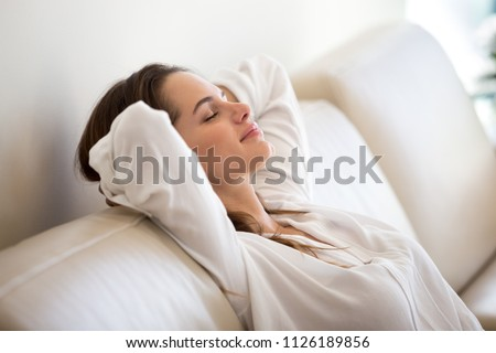 Calm millennial woman relaxing on soft comfortable sofa meditating or having daytime nap, carefree lazy girl breathing fresh air enjoying no stress free peaceful weekend morning resting on couch #1126189856
