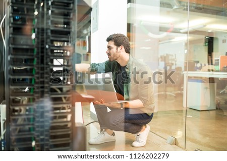Network administrator with notebook computer sitting in data center room and working with networking device on rack cabinet #1126202279