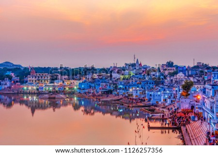 Pushkar Holy Lake at sunset. Hindu pilgrims bathing in sacred Lake Pushkar (Sarovar) on ghats. Countless people in colourful attire gather to take a dip in the Holy Lake and pray to deities. #1126257356