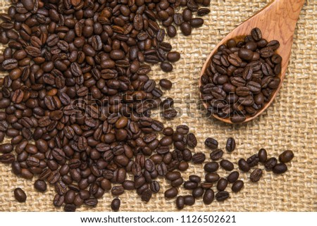 Coffee beans on wooden spoons. scattered Coffee beans on Linen Fabric.  #1126502621