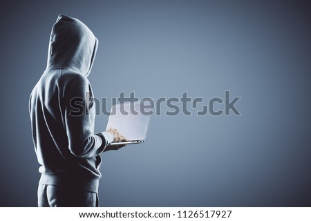 side view on hacker in grey hoody with laptop at grey background. #1126517927