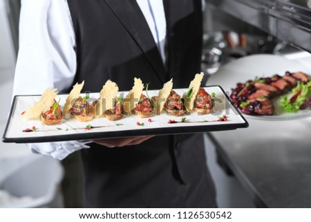 The waiter with the ready prepared dishes in the restaurant kitchen. #1126530542