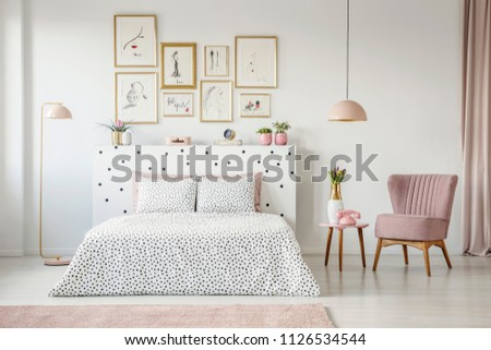 Pink armchair next to patterned bed in feminine bedroom interior with gallery of posters #1126534544