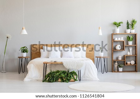 White pillows on wooden bed in minimal bedroom interior with plants and round rug. Real photo #1126541804