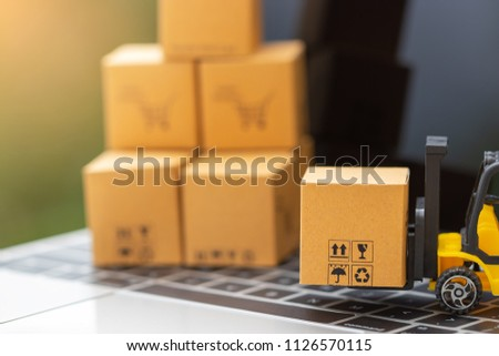 Mini forklift truck load cardboard box and stack of boxes behind on laptop keyboard with nature background. Logistics and transportation management ideas and Industry business commercial concept. #1126570115