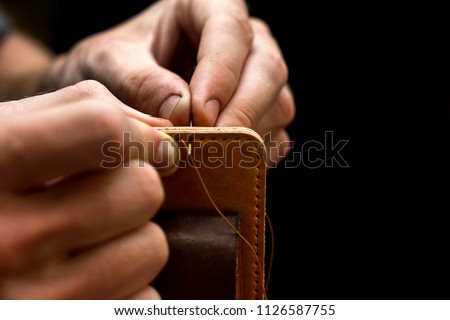 Working process of the leather belt in the leather workshop. Man holding crafting tool and working. He is sewing to make a walet. Tanner in old tannery. Wooden table background Royalty-Free Stock Photo #1126587755