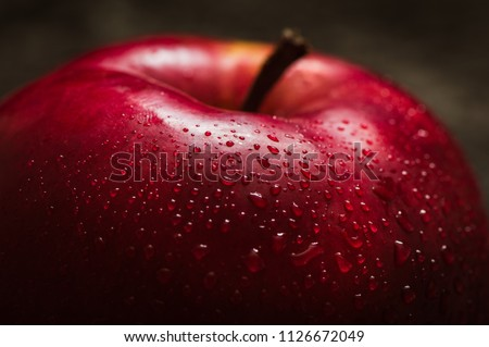 Red apple close-up. Fresh red apple on a black texture background. Apples with droplets of water. Text space. Healthy food for vegetarians.