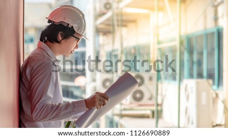 Engineer or Architect checking architectural drawing while wearing a personal protective equipment safety helmet at construction site. Engineering, Architecture and construction business concepts #1126690889