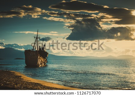 An old abandoned shipwreck, wrecked boat sunken ship stand on beach coast. Scenic seascape #1126717070