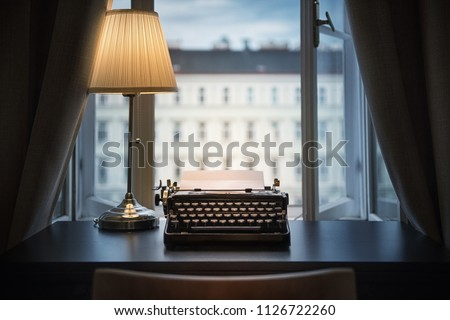 Workplace of a writer, journalist, creator. An old typewriter and a lamp on the table. Retro style. The concept on scientific, historical, literature, education and philosophical topics.  #1126722260